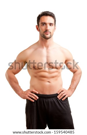 Fit man standing shirtless with his arms at his waist in a white background - stock photo