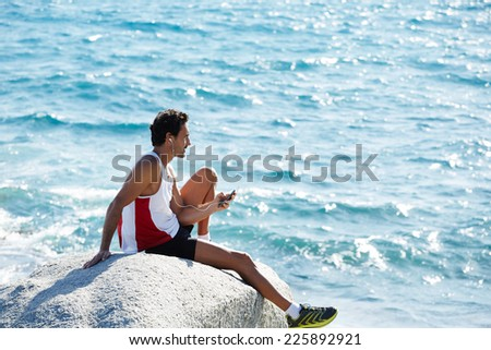 Fit man taking break after workout outdoors, athlete man in sportswear listen to music and enjoying the sun sitting on sea rocks, male runner enjoying amazing sea view and sunny day, sport lifestyle - stock photo