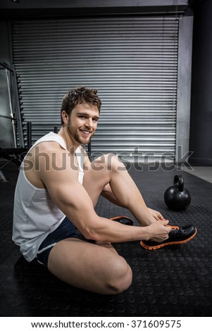 Fit man tying his shoelaces at crossfit gym - stock photo