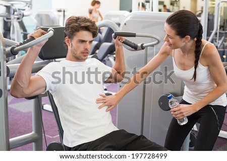 Fit man using weights machine for arms with his trainer at the gym - stock photo