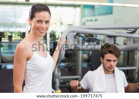 Fit man using weights machine with trainer smiling at camera at the gym