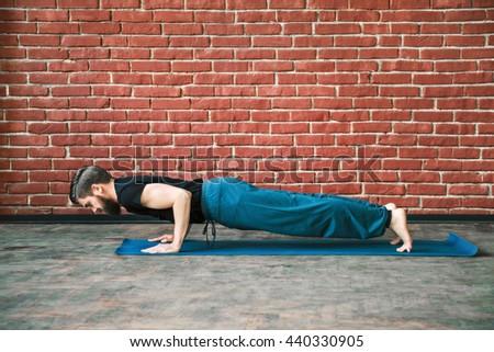 Fit man with a beard wearing black T-shirt and blue trousers doing yoga position on blue matt at wall background, copy space, chaturanga dandastana asana. - stock photo