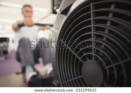 Fit man working out on rowing machine at the gym - stock photo