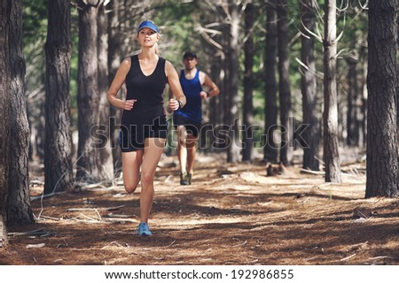 Fit marathon couple trail running together for sport and healthy living - stock photo