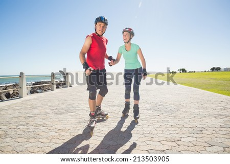 Fit mature couple rollerblading on the pier on a sunny day - stock photo