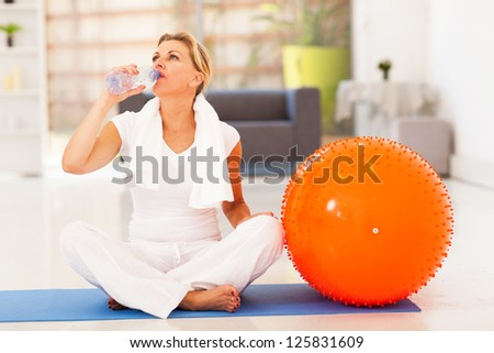 fit mature woman drinking water after exercise at home - stock photo
