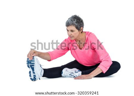 Fit mature woman exercising against white background