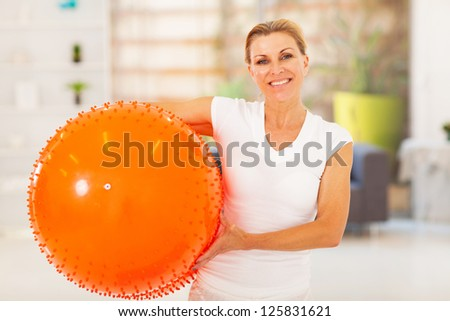 fit mature woman holding exercise ball at home - stock photo