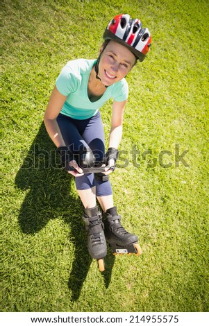 Fit mature woman in roller blades on the grass on a sunny day - stock photo