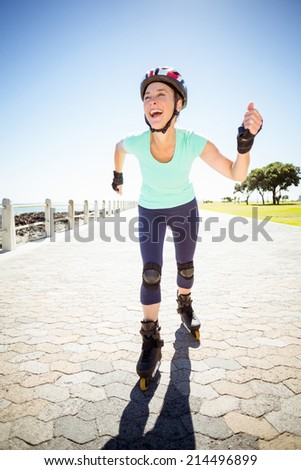 Fit mature woman rollerblading on the pier on a sunny day - stock photo