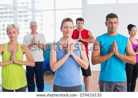 Fit men and women meditating with hands joined in fitness club - stock photo
