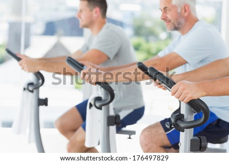 Fit men exercising on fitness bikes at gym - stock photo