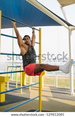 Fit men training abs by raising legs on a horisontal bar. Fitness arabian men workout doing exercises at outdoor
