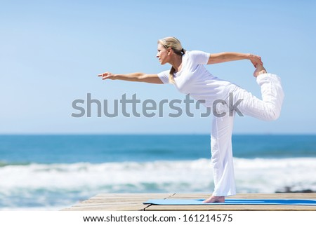 fit middle aged woman in white doing yoga exercise at the beach - stock photo