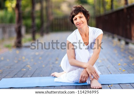 fit middle aged woman relaxing after workout - stock photo