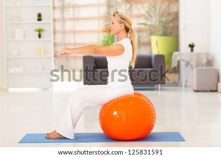 fit middle aged woman sitting on exercise ball at home - stock photo