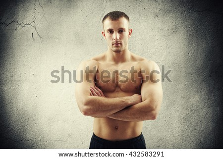 Fit muscular bare-chested man is standing over cracked concrete wall with his arms crossed on chest