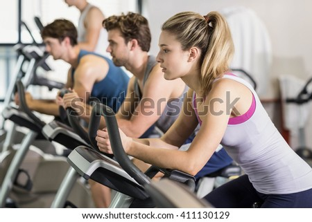 Fit people doing exercise bike at gym - stock photo