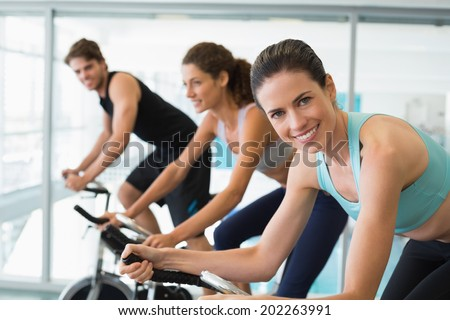 Fit people in a spin class with brunette smiling at camera at the gym