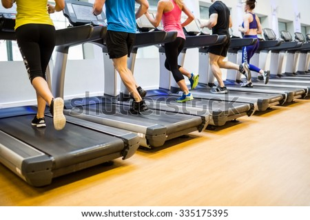 Fit people jogging on treadmills at the gym - stock photo