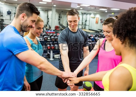 Fit people putting their hands together at the gym - stock photo