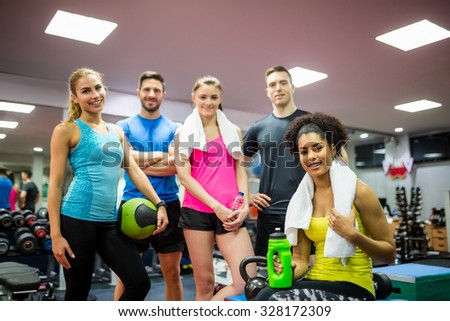 Fit people smiling at camera in weights room at the gym