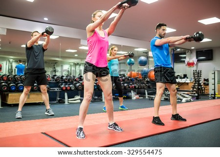 Fit people swinging kettlebell weights at the gym - stock photo