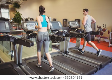 Fit people using the treadmill at the gym - stock photo