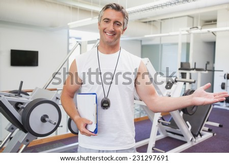 Fit personal trainer smiling at camera in fitness studio at the gym - stock photo