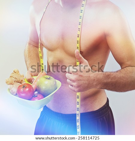 Fit shirtless Caucasian young man with fresh fruits, vegetables and tape measure. Retouched, square format, light effect filter, unrecognizable person. - stock photo