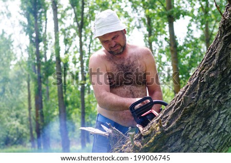 Fit shirtless man wearing a hat carrying a portable petrol chainsaw in woodland as he prepares to fell a tree for fuel
