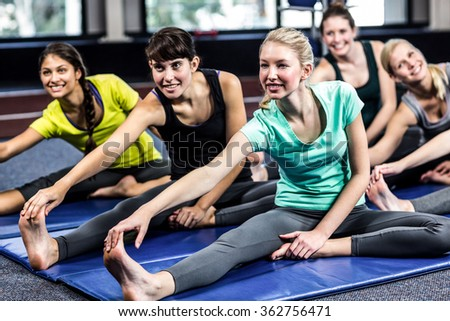 Fit smiling group doing stretching in gym