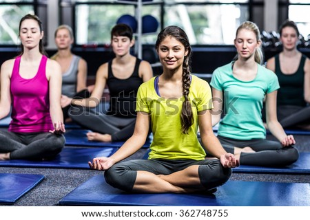 Fit smiling group doing yoga in gym - stock photo
