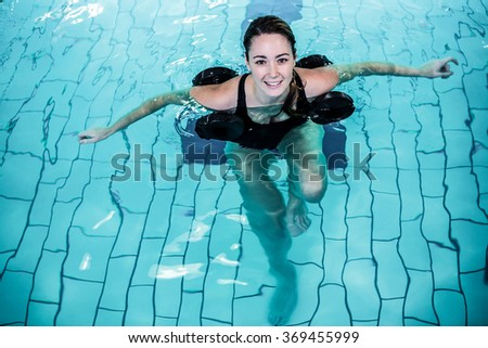 Fit smiling woman doing aqua aerobics in swimming pool - stock photo