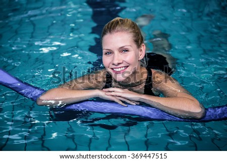 Fit smiling woman with a foam roller in swimming pool - stock photo