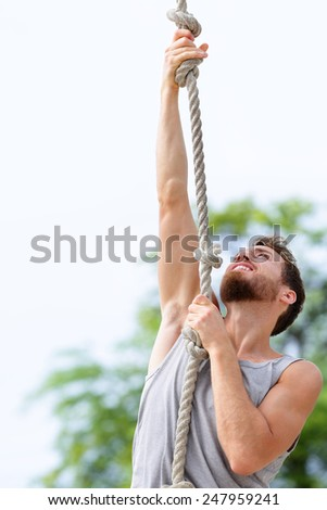 Fit strong man cross training climbing rope. Male adult exercising rope climb as part of crossfit workout routine outdoors on beach gym. - stock photo