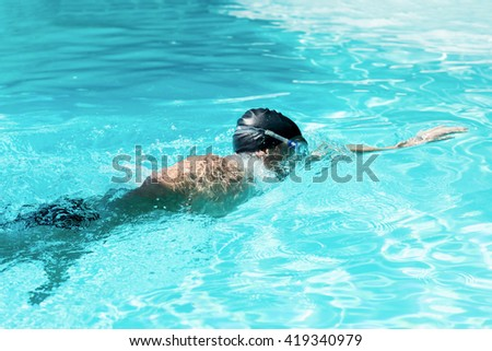 Fit swimmer doing the front crawl in swimming pool