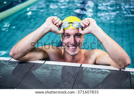 Fit swimmer lean on edge of the swimming pool at leisure center - stock photo
