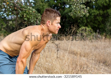 Fit tired man resting outside in nature - stock photo