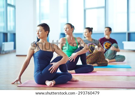 Fit trainer and her group working out in gym