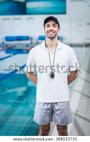 Fit trainer standing next to the pool - stock photo