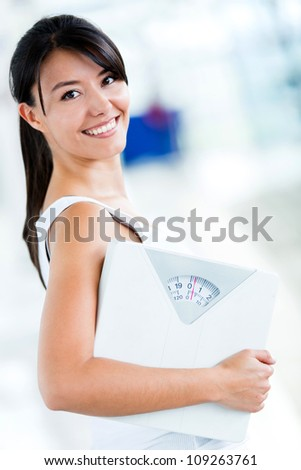 Fit woman at the gym holding a weight scale - stock photo
