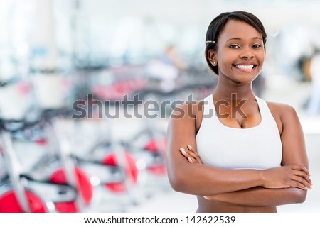Fit woman at the gym looking very happy and confident - stock photo