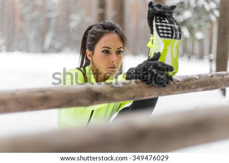 Fit woman athlete doing hamstring leg stretching exercises outdoors in woods. Female sports model exercising outdoor winter park - stock photo