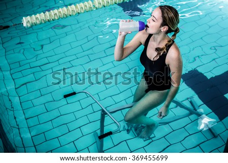 Fit woman cycling while drinking water in swimming pool - stock photo