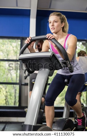 Fit woman doing exercise bike at gym - stock photo