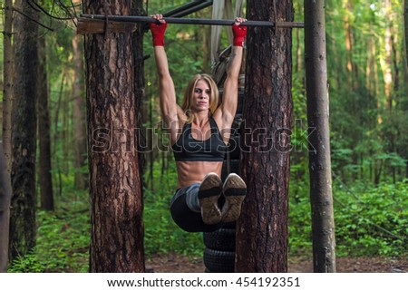 Fit woman doing hanging leg lifts abs muscles exercise on horisontal bar working out outside. - stock photo