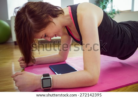 Fit woman doing plank on mat at home in the living room - stock photo