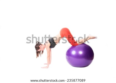 Fit woman doing push-ups on purple exercise ball-isolated on white