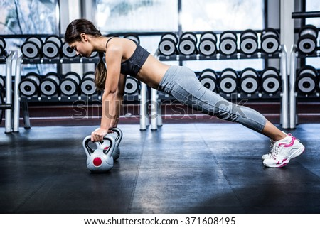 Fit woman doing push ups with kettlebells at gym - stock photo